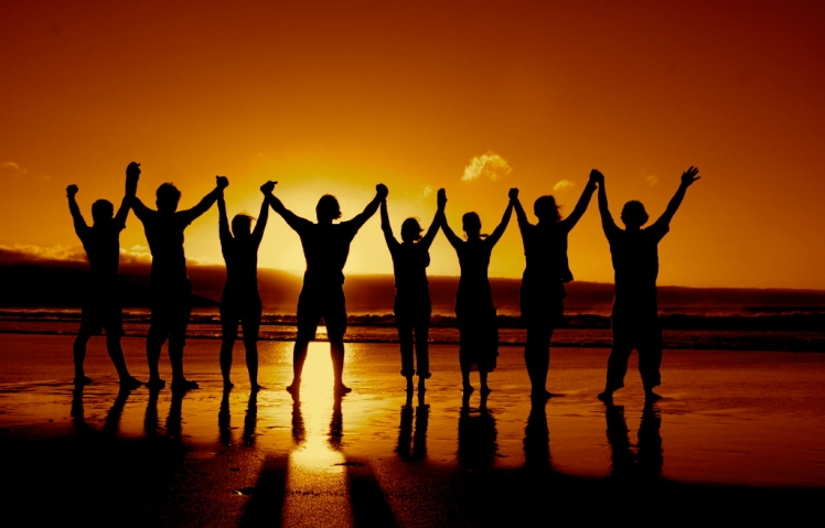 silhouette of a group of people holding raised hands