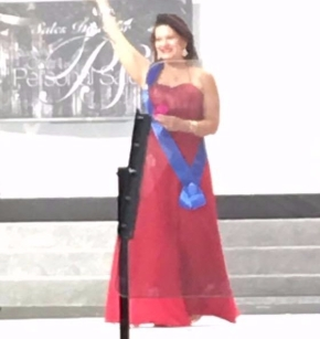 Catarina walking across the Mary Kay stage in her red gown